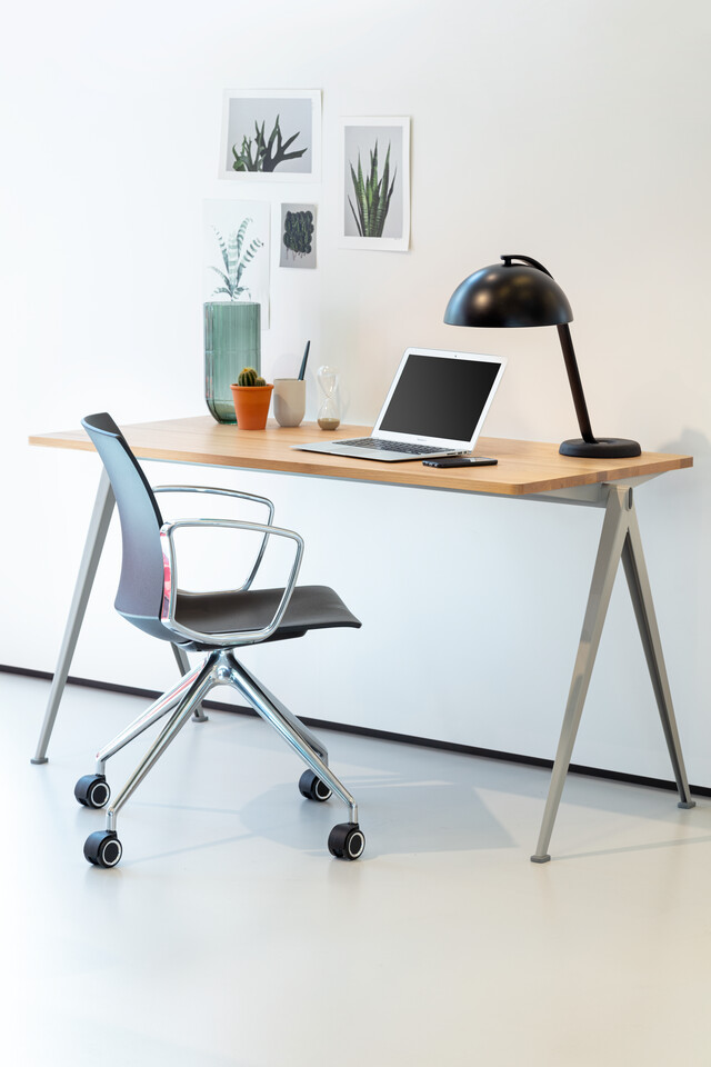 Royal Ahrend Well trestle base chair on castors with polished chrome frame and armrests with anthracite shell turned open and Pyramid table left rear view