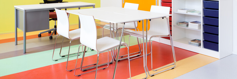 Royal Ahrend 456 seminar tables with chrome frame and white tops with 370 wireframe chairs in classroom front right view