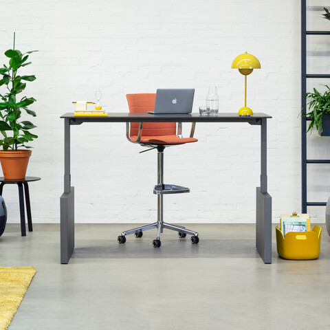 Royal Ahrend Balance Lift workstation in grey with charcoal top in stand position and Well Work chair upholstered in red front view