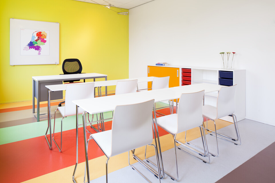 Royal Ahrend 456 seminar tables with chrome frame and white tops in 2 rows of 3 with 370 wireframe chairs in classroom rear left view