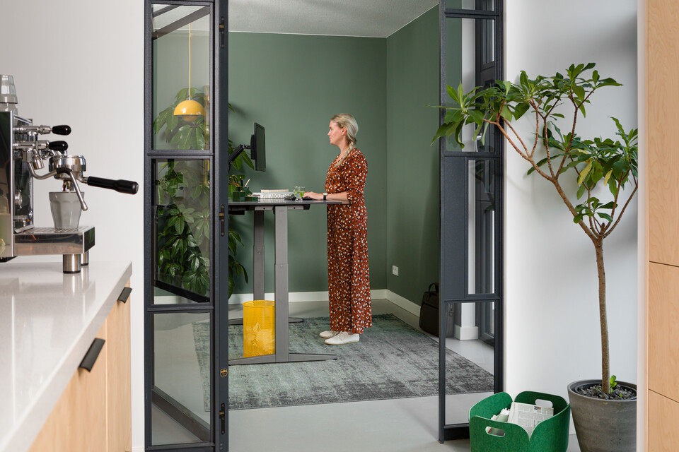 Royal Ahrend balance workstation in grey with charcoal tabletop in standing position with female model interior view