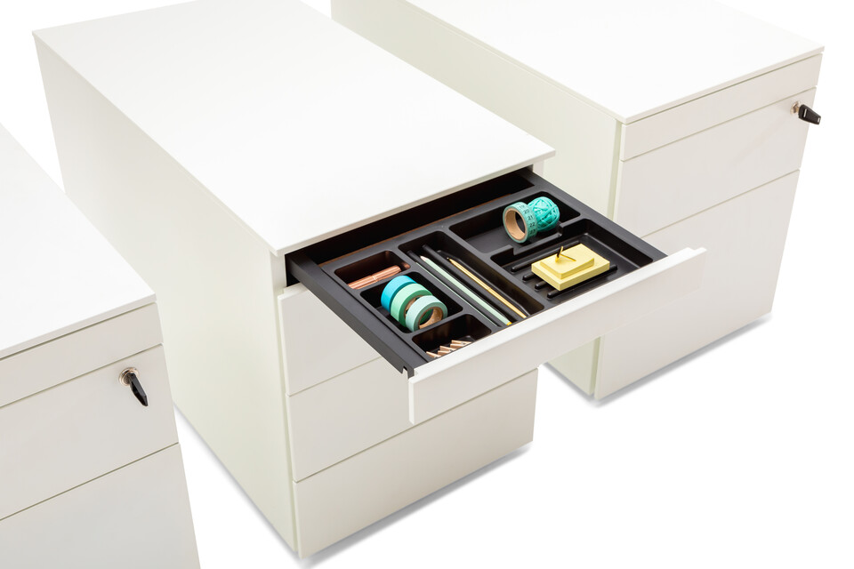 Royal Ahrend Pedestals in white with open pen trays and turquoise office supplies front left detail view