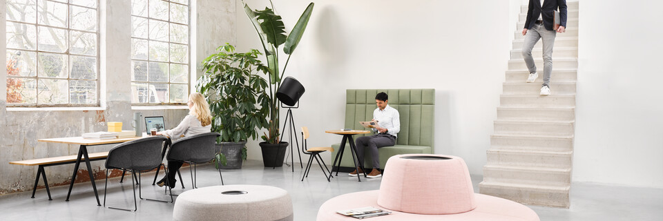 Ahrend Recharge poufs upholstered in pink yellow and grey with Pyramid and Well armchairs with models in a Hybrid working community setting