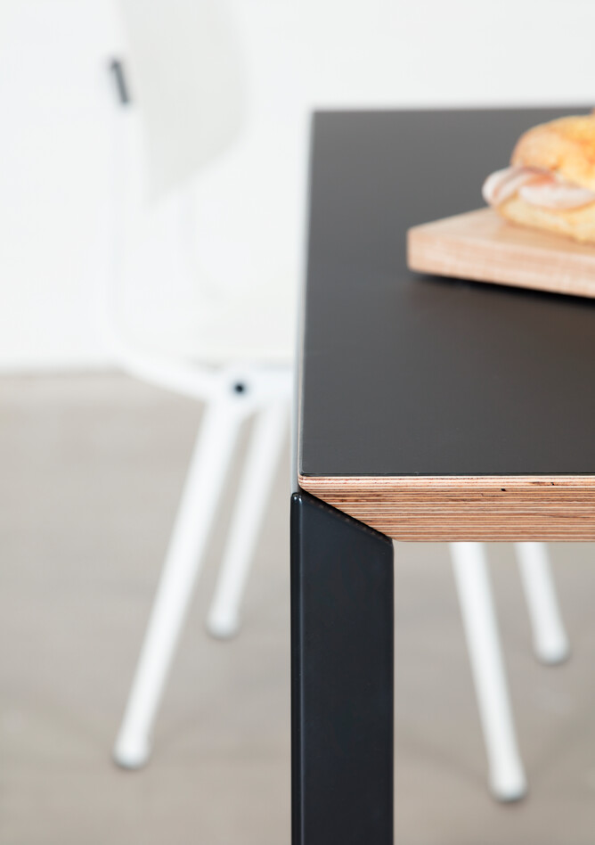 Royal Ahrend Delta table in black with black tabletop with white Revolt chair blurred and sandwich right side view