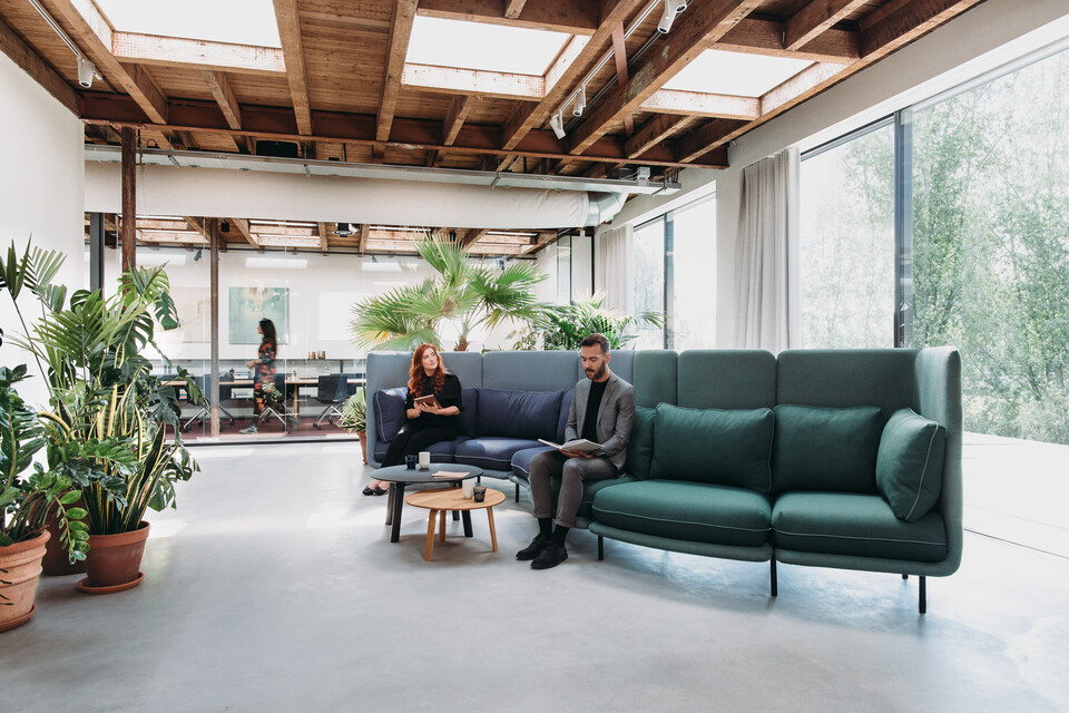 Royal Ahrend Embrace sofa upholstered in green and blue with female and male model at HofmanDurjandin office in Diemen EB005