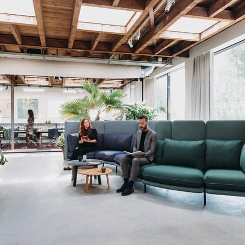 Royal Ahrend Embrace sofa upholstered in green and blue with female and male model at HofmanDujardin office in Diemen EB005