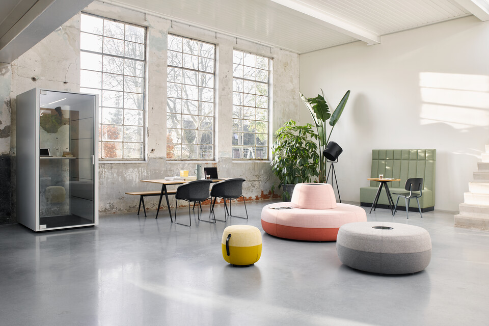 Ahrend Recharge poufs upholstered in pink yellow and grey with Qabin and Pyramid with Well armchairs in a Hybrid working community setting