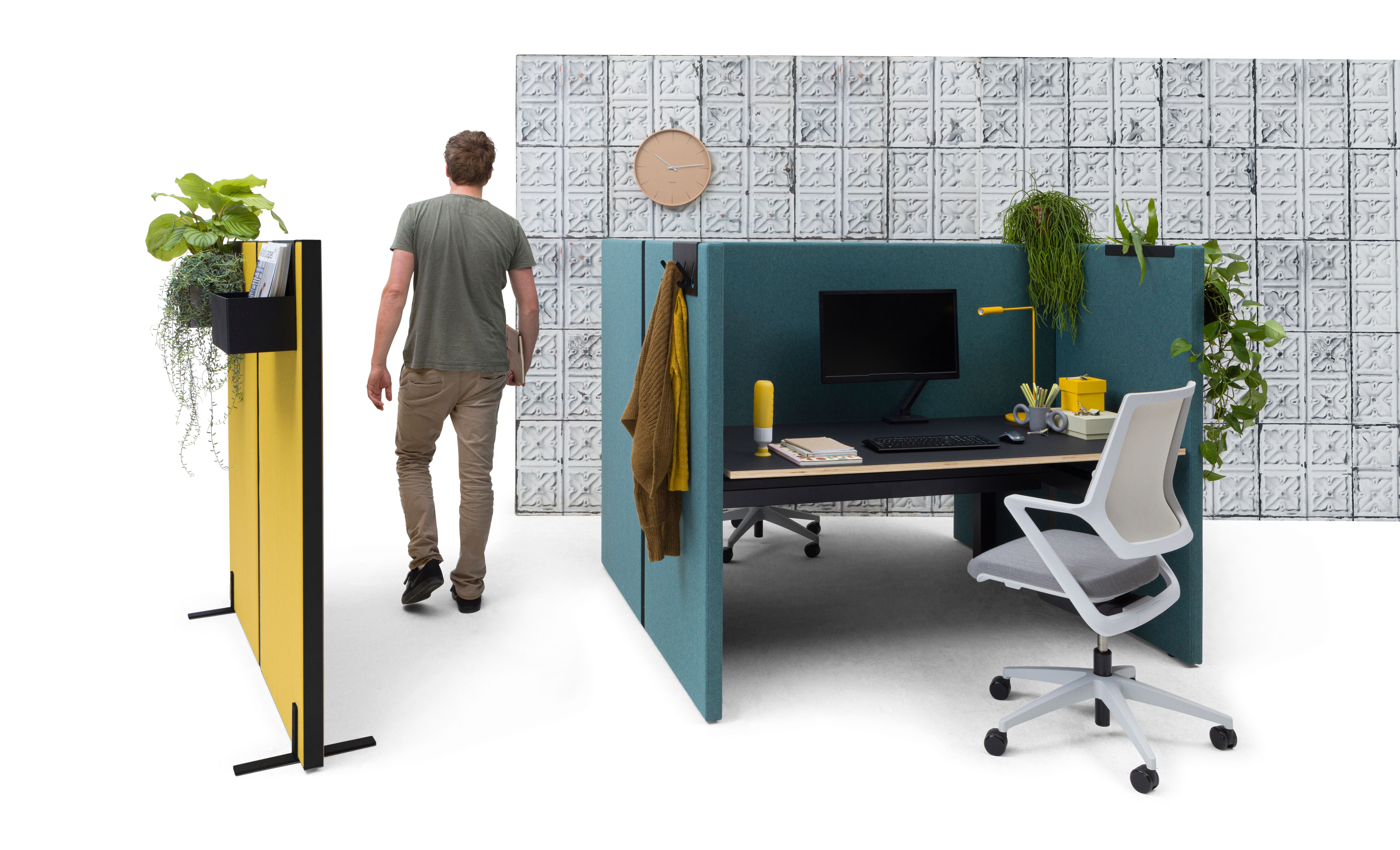Gispen SEPP Acoustic screen with black TMNL dual workstation upholstered in turquoise and yellow with male model behind and grey Zinn Multi chair with tins04 backpanel front left view
