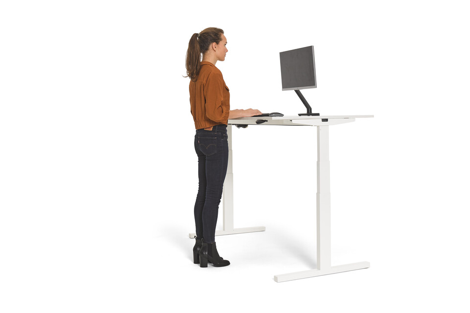 Gispen Home office desk in white and in standing position with female model and eye sight lined with top monitor for ergonomic working front right view