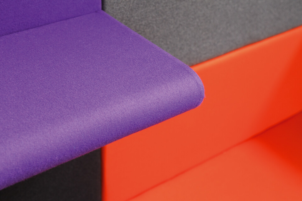 Royal Ahrend Living Wall panels upholstered in grey with purple armrest panel and orange seating panel front left view
