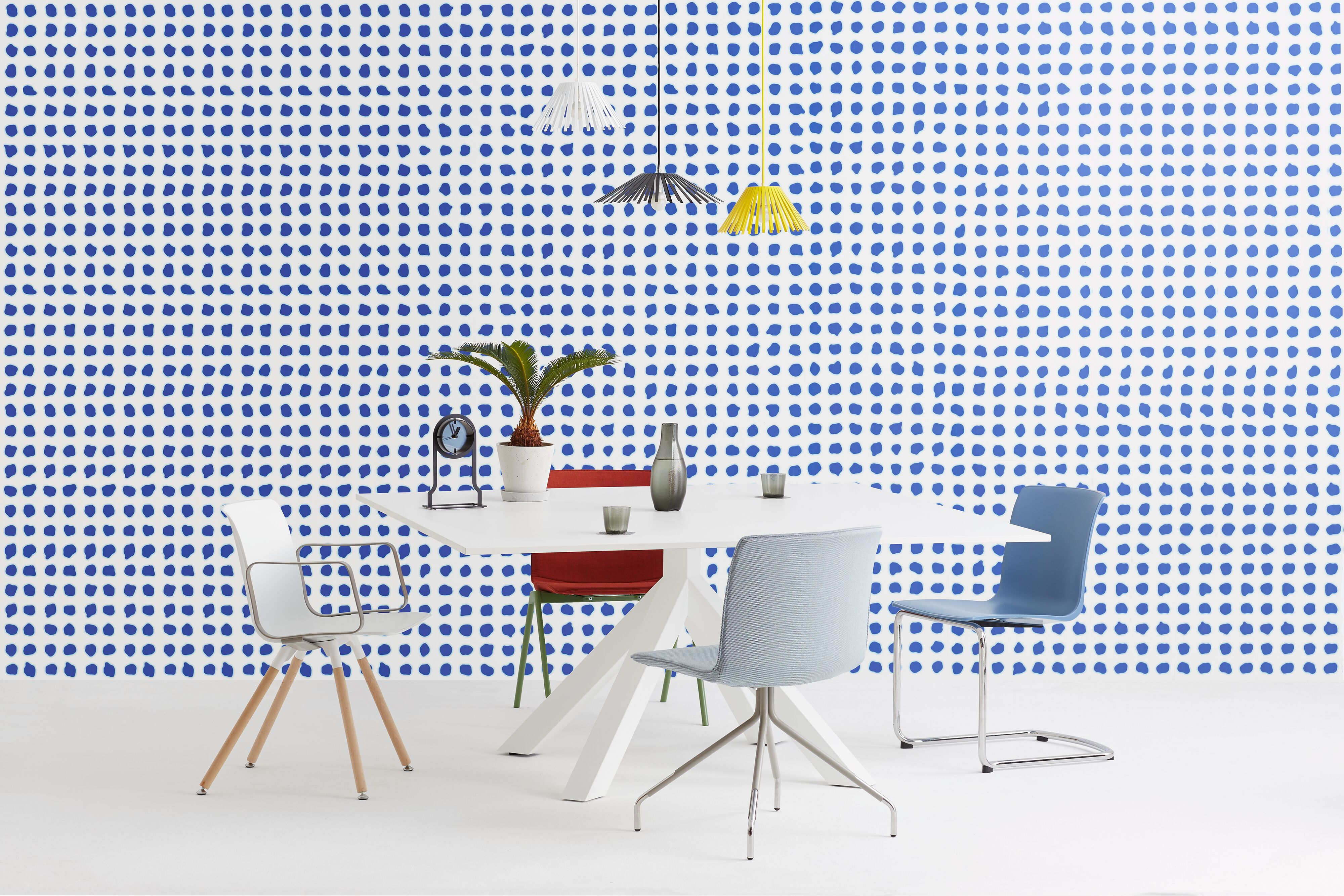 Gispen Dukdalf table with white frame and white tabletop with Nomi Chairs and Ray pendant lamps and Outline clock in front of blue dotted background front view