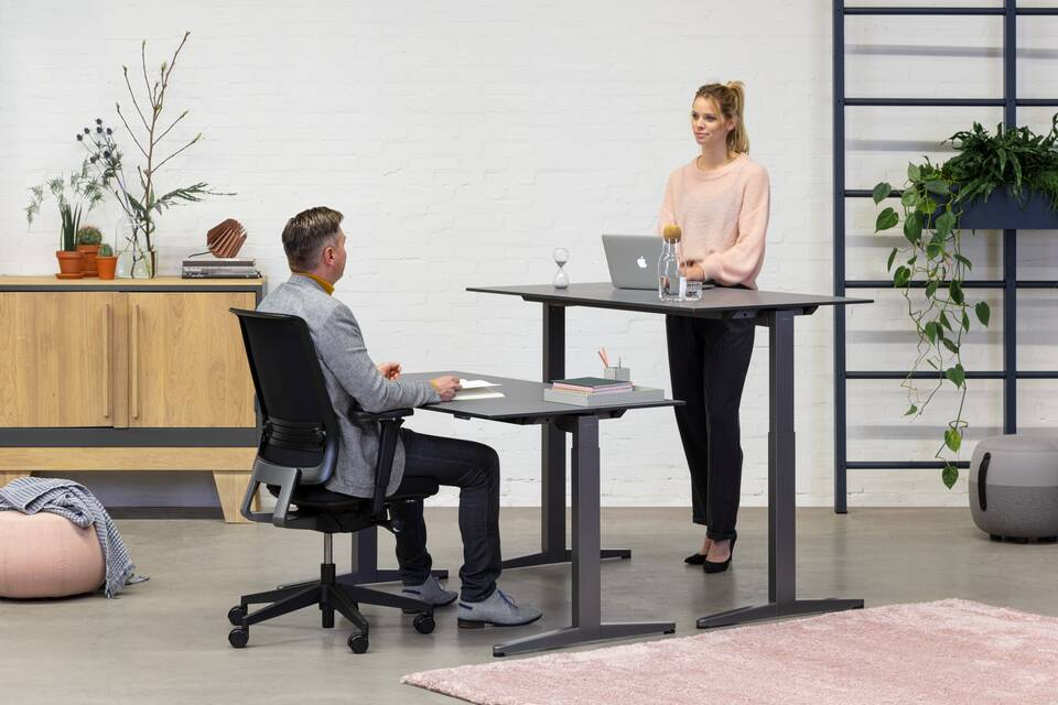 Royal Ahrend Balance Lift workstations in grey with charcoal tops and Ease office chair in black with male and female model sitting and standing front right view