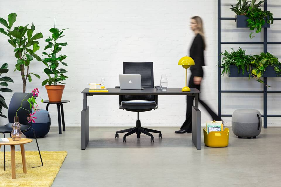 Royal Ahrend Balance Lift workstation in grey with charcoal top and 2020 office chair with female model walking front view