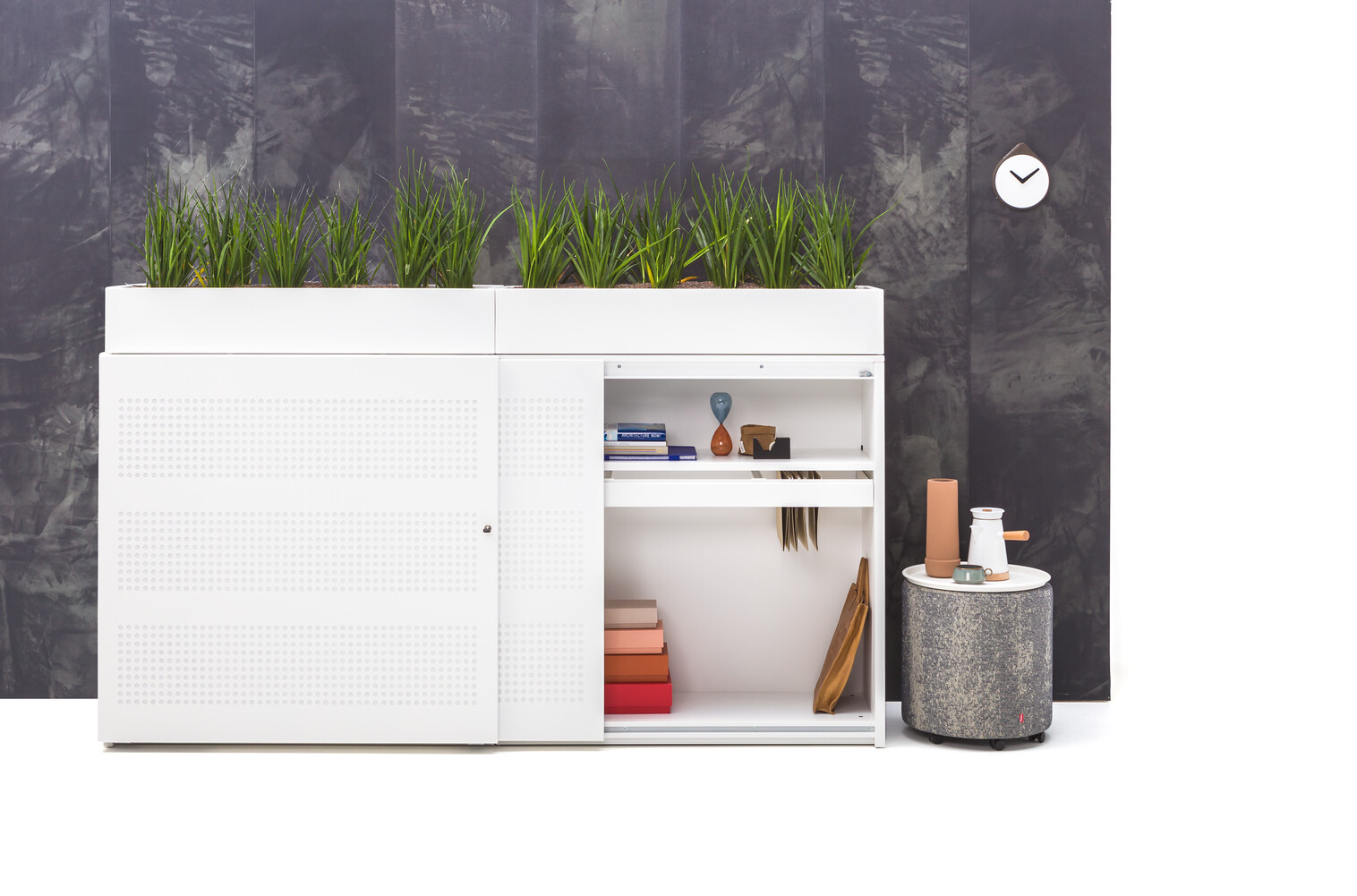 Gispen SDK sliding door cabinet in white with round perforated doors and right door opened with planters and Asido stool with Asy tray in front of black panel front view