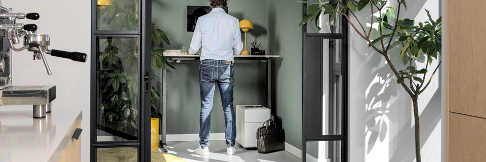 Royal Ahrend balance workstation in grey with oak tabletop in standing position with male model interior view