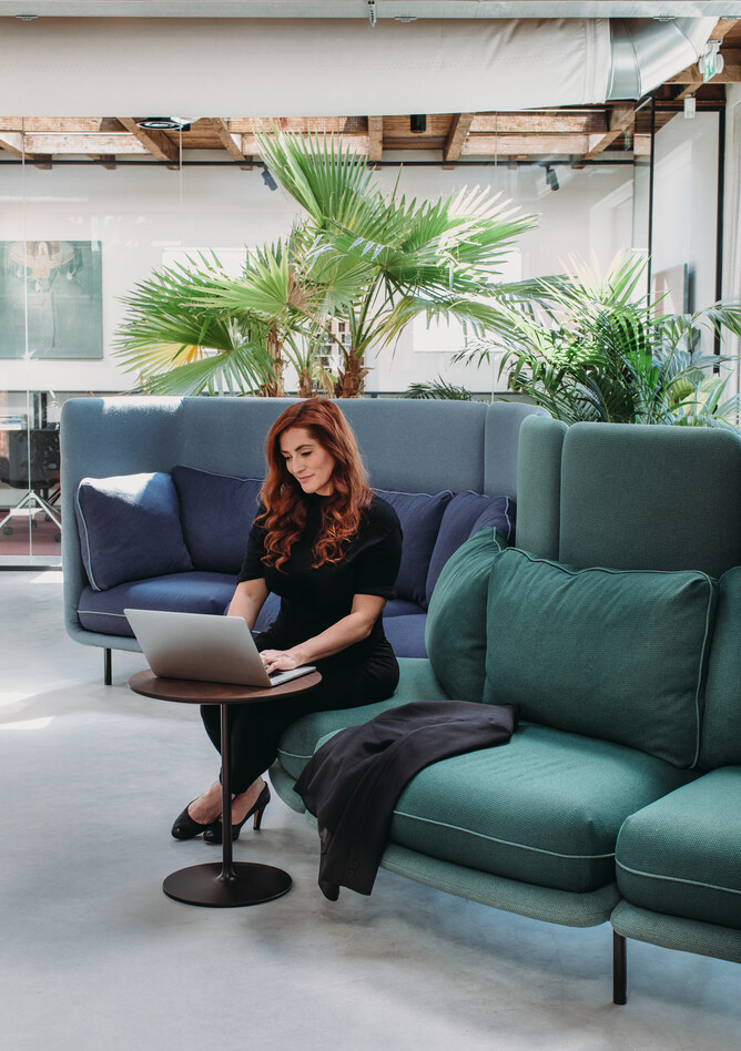 Royal Ahrend Embrace sofa upholstered in green and blue with female model at HofmanDurjandin office in Diemen EB009