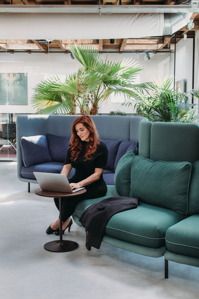 Royal Ahrend Embrace sofa upholstered in green and blue with female model at HofmanDujardin office in Diemen EB009