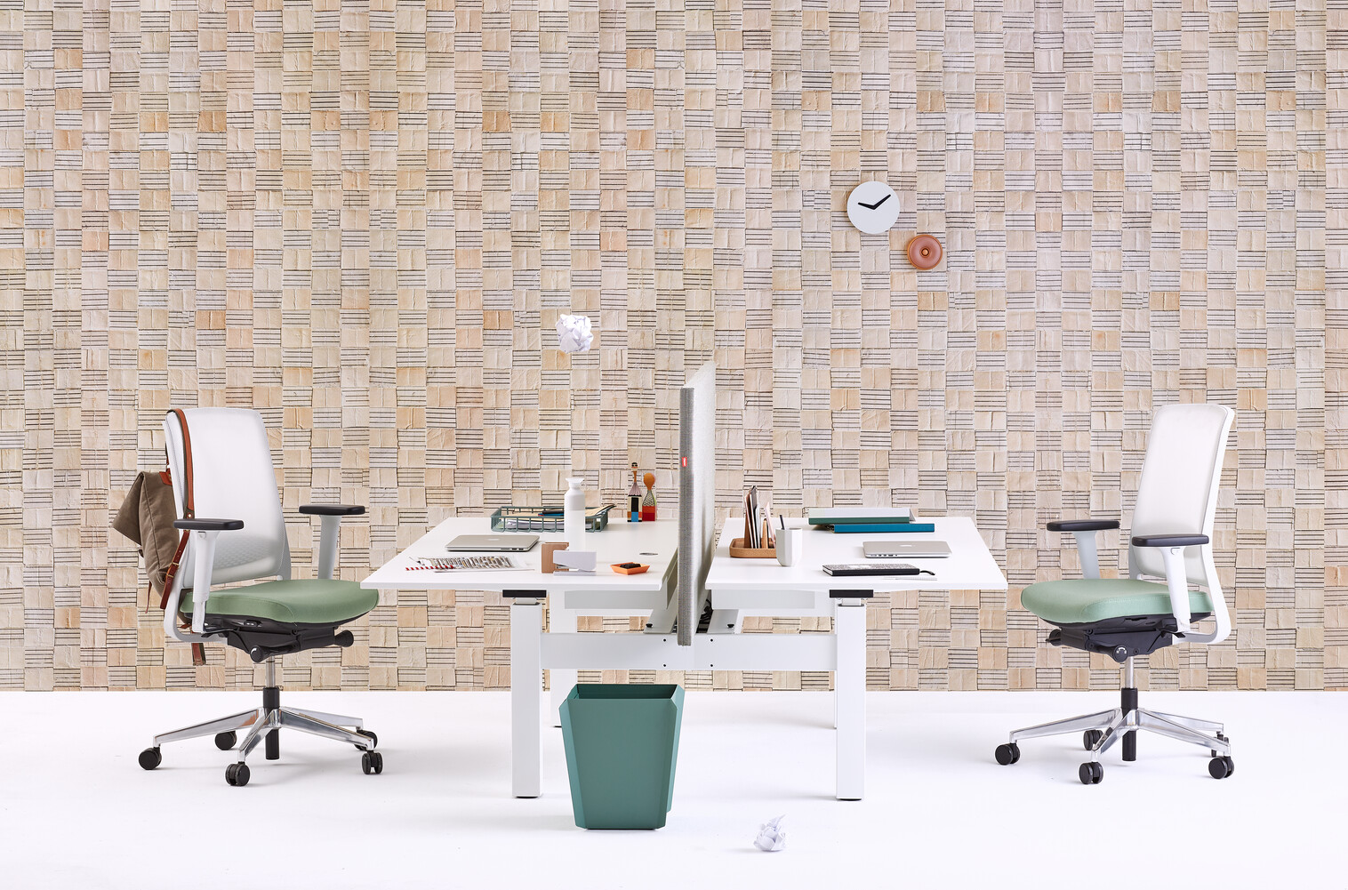 Gispen TM dual table with white frame and white tabletop  and 2 Zinn office chairs and green Binit wastebin in front of light brown pattern background front view