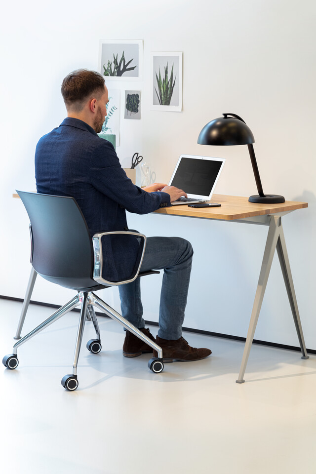 Royal Ahrend Well trestle base chair on castors with polished chrome frame and armrests with anthracite shell and male model with Pyramid table left rear view