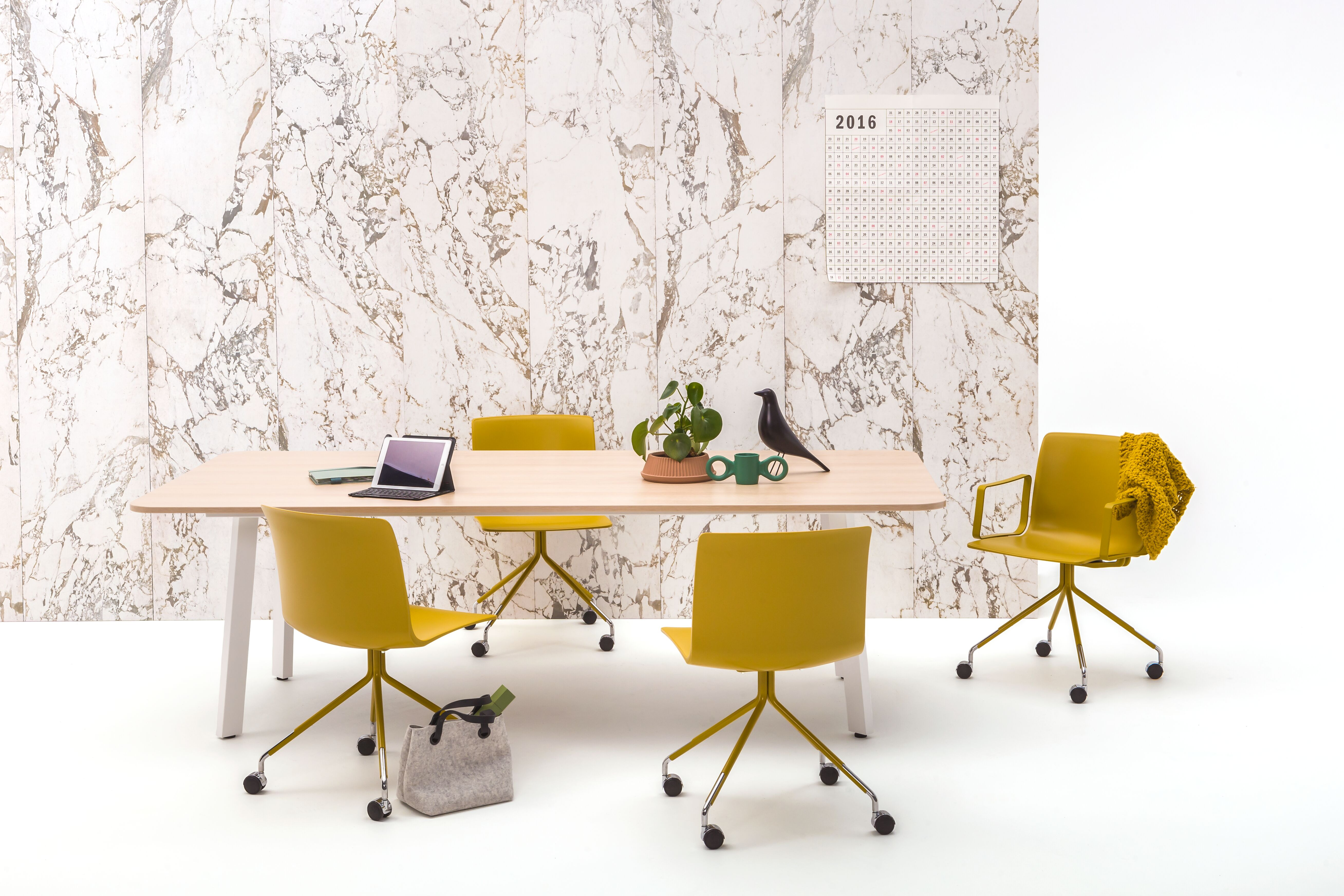 Gispen TEAM Classic conference table with white frame and oak tabletop and yellow Nomi Work chairs in front of marble backpanel front view