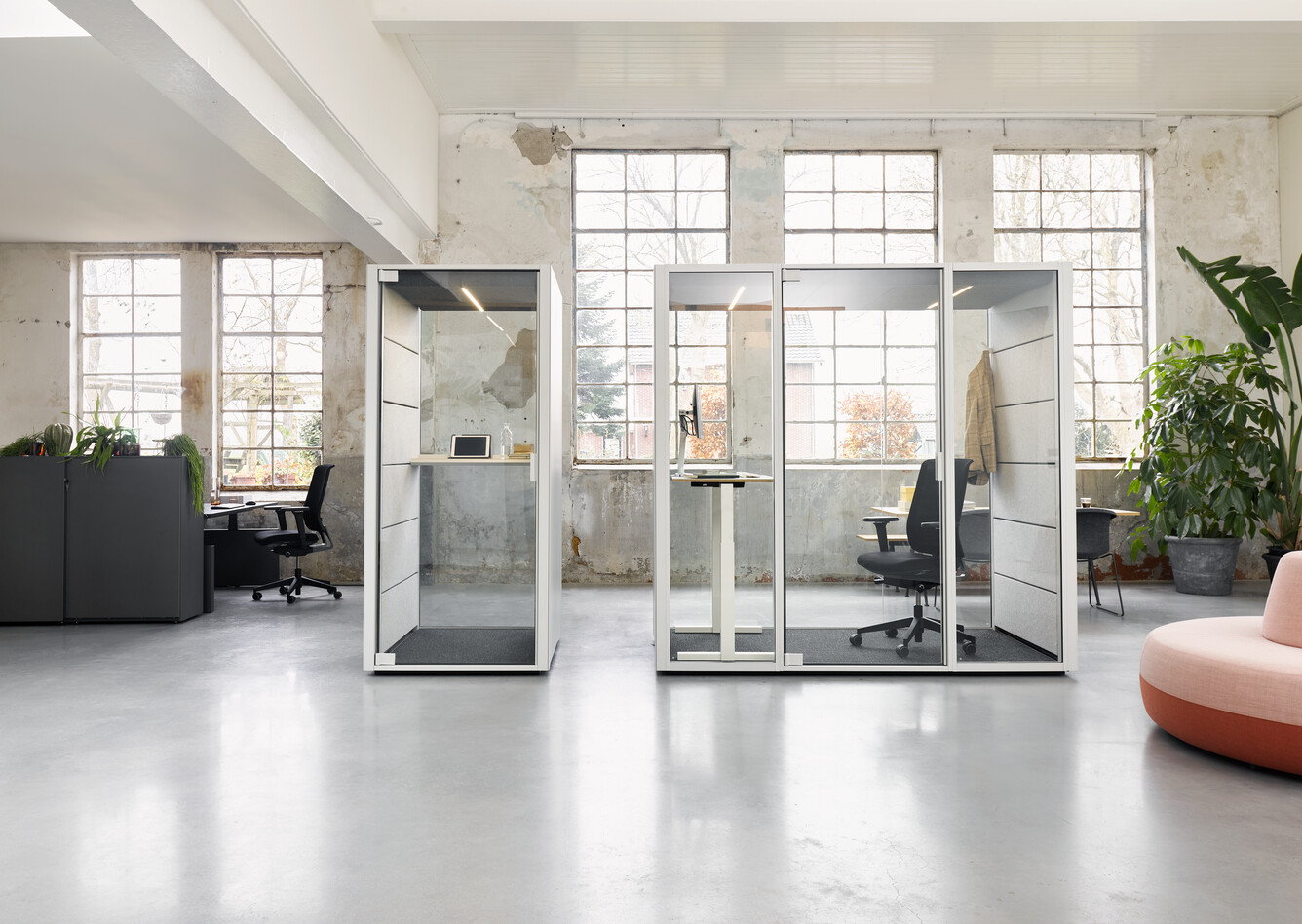Ahrend Qabin booth and space in space with Ease office chair and white stand desk with Balance SDK Recharge and Well in a Hybrid working community setting