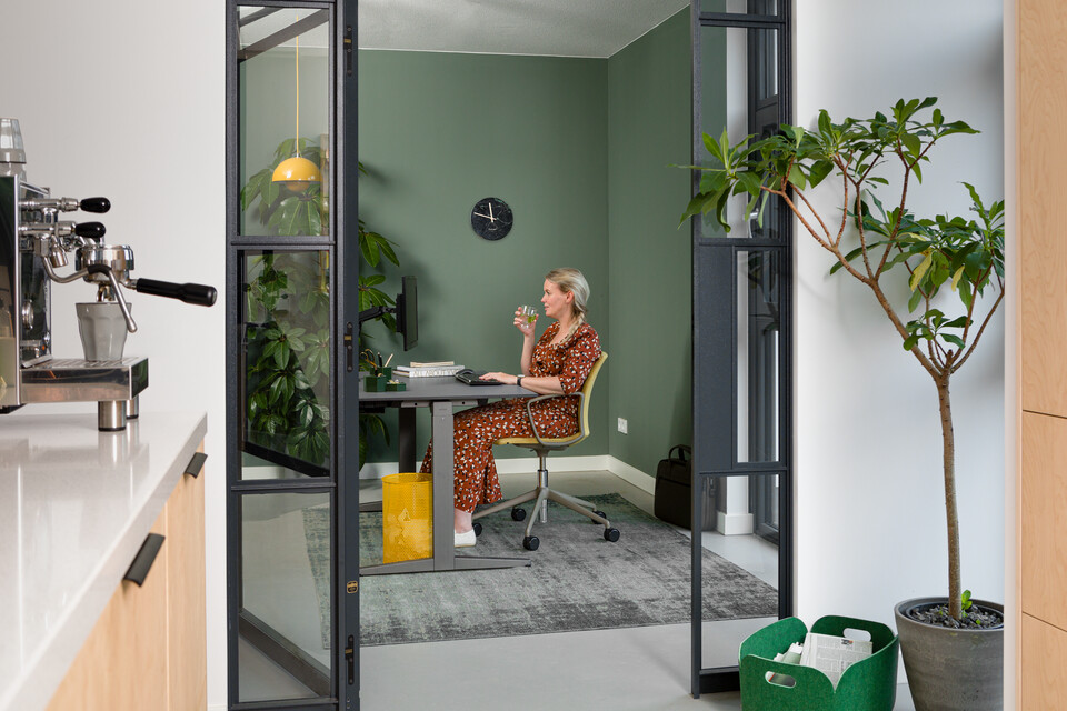 Royal Ahrend balance workstation in grey with charcoal tabletop and Well chair upholstered in yellow and female model interior view