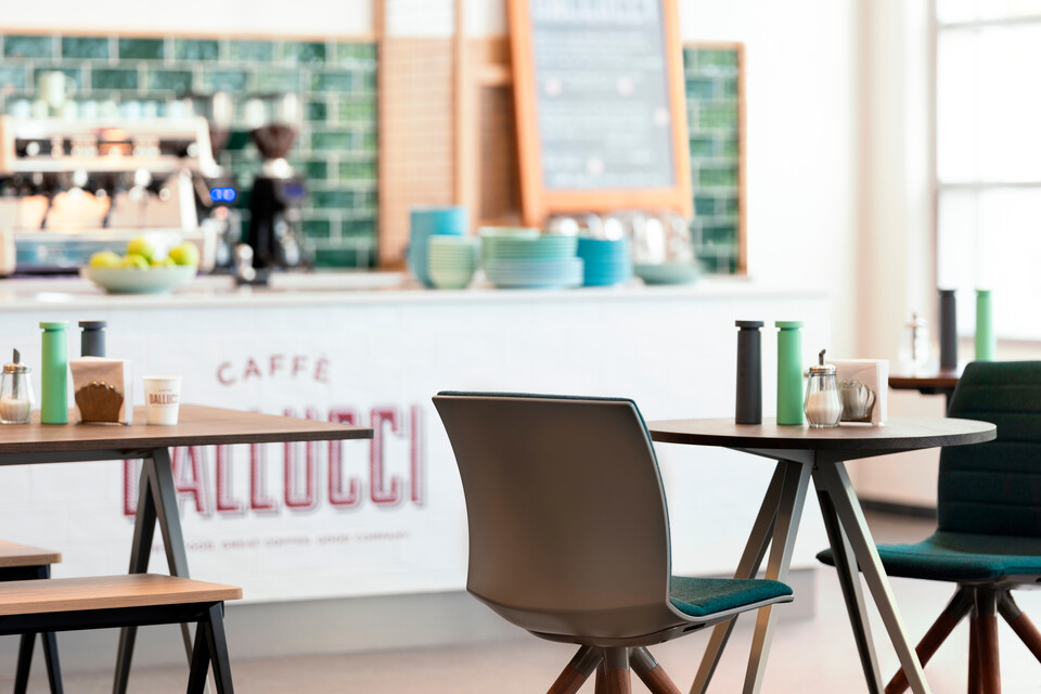 Royal Ahrend Well trestle wood base chairs with grey shells and green front upholstered at Caffe Dallucci in Amsterdam DSF3291