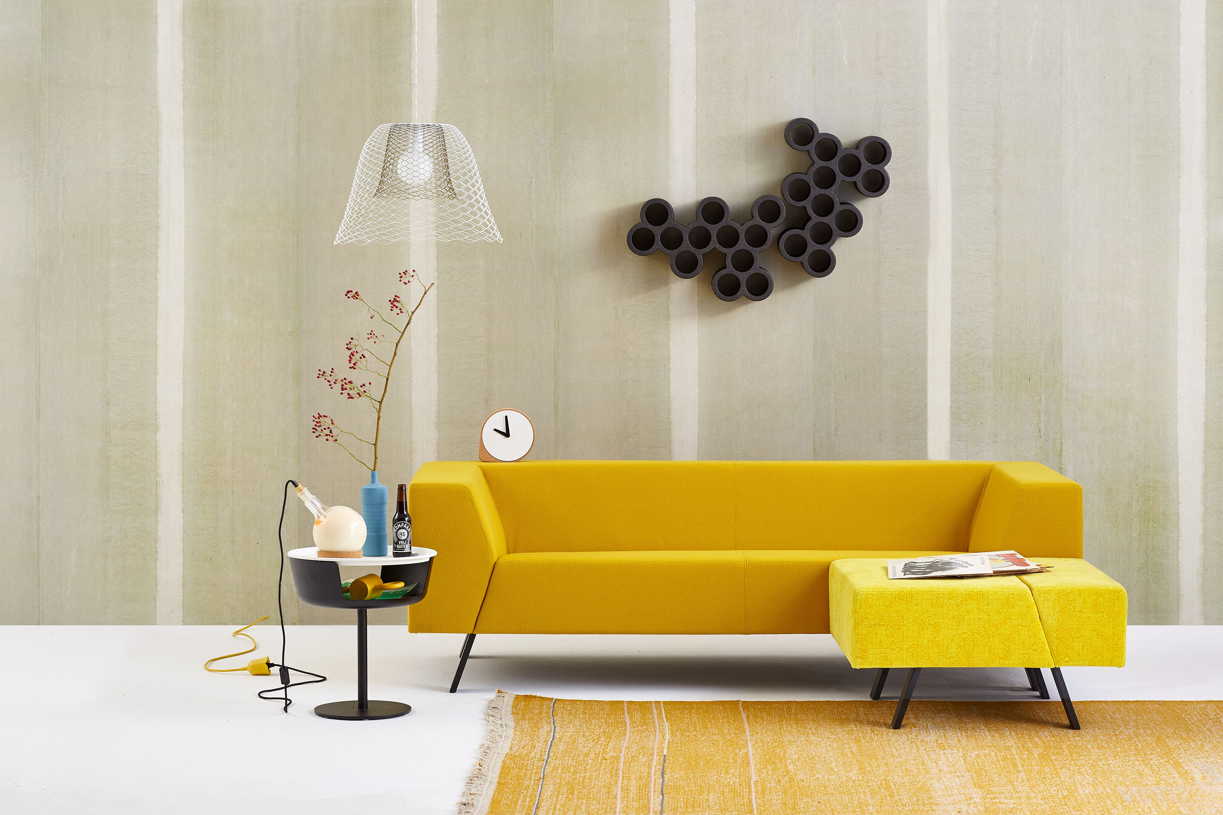 Gispen Sett sofa with yellow upholstery and Asy sidetable and dombo cup with Slingerlamp pendant lamp and carpet in front of light green background front view