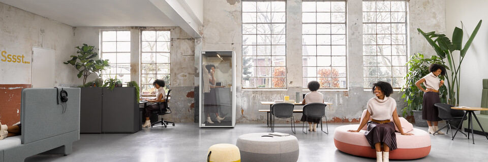 Ahrend Loungescape Powernap and SDK Balance with Ease and Qabin with Recharge Pyramid and Well armchairs with female model in a Hybrid working community setting
