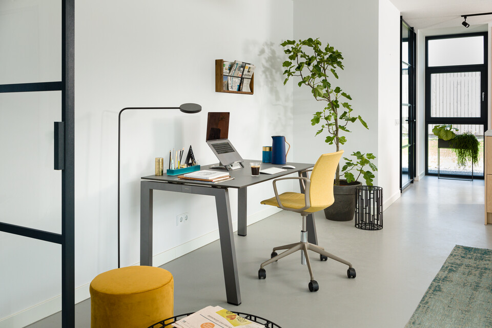 Royal Ahrend balance workstation in grey with charcoal tabletop and Well chair in gray and upholstered in yellow interior view