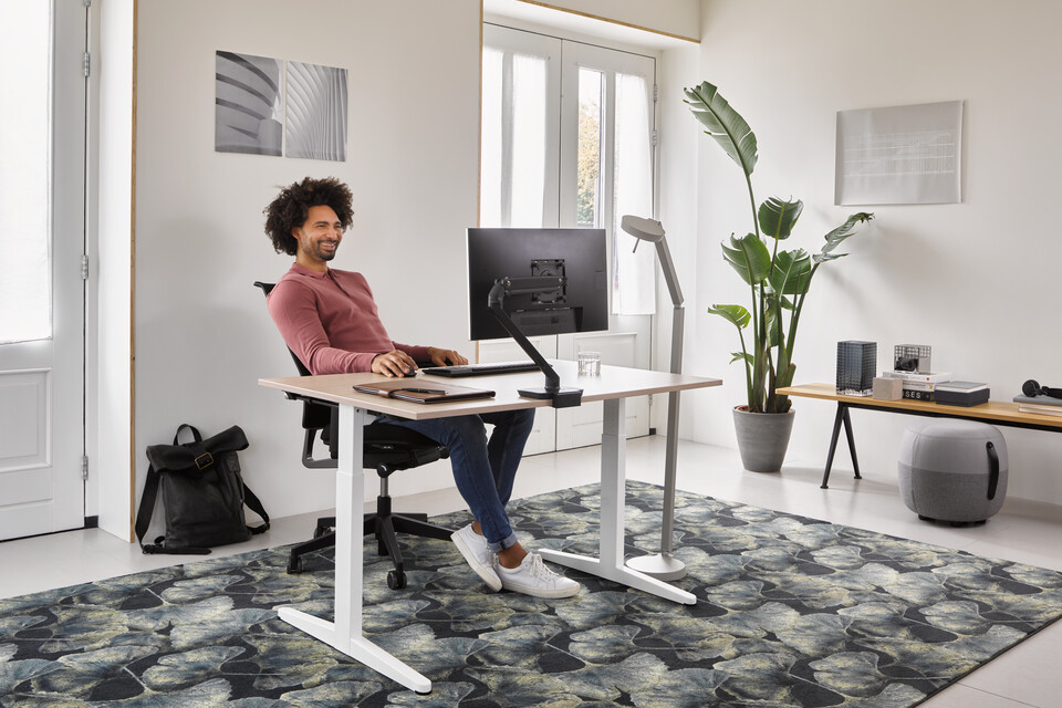 Ahrend Home HVM desk in white with oak tabletop and black Ease office chair with grey Recharge and Pyramid bench with male model in a work from home setting