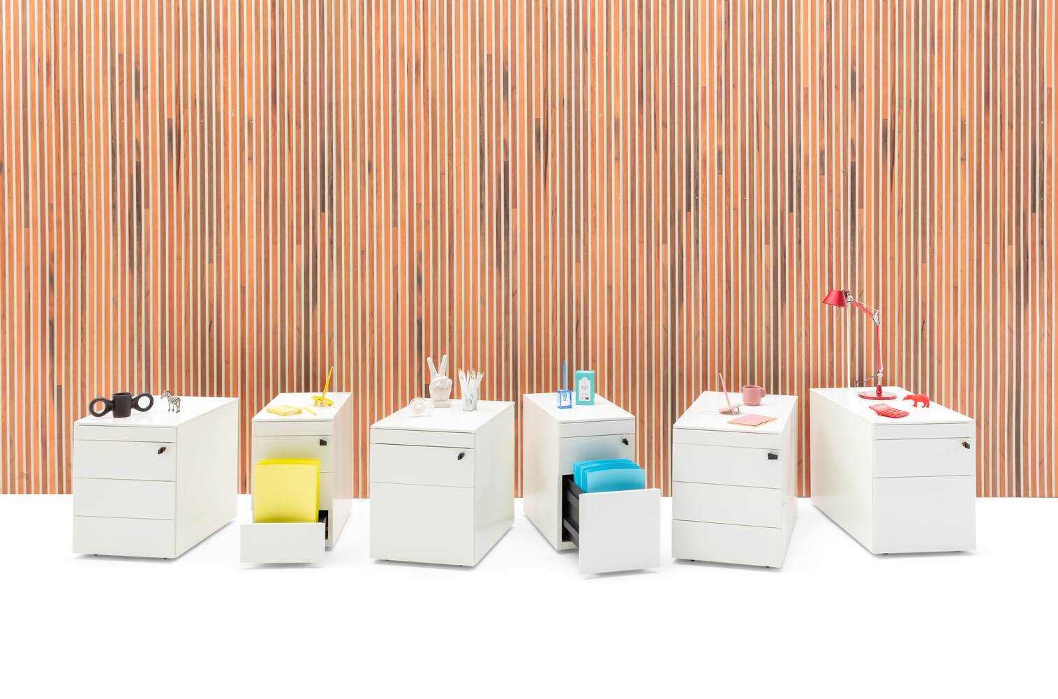 Royal Ahrend Pedestals in white with coloured office supplies in front of brown wood patern backpanel front view