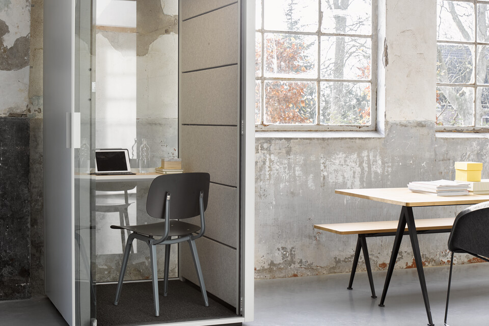 Ahrend Qabin booth in grey with anthracite Revolt chair and grey Recharge with Pyramid and Well armchair in a Hybrid working community setting