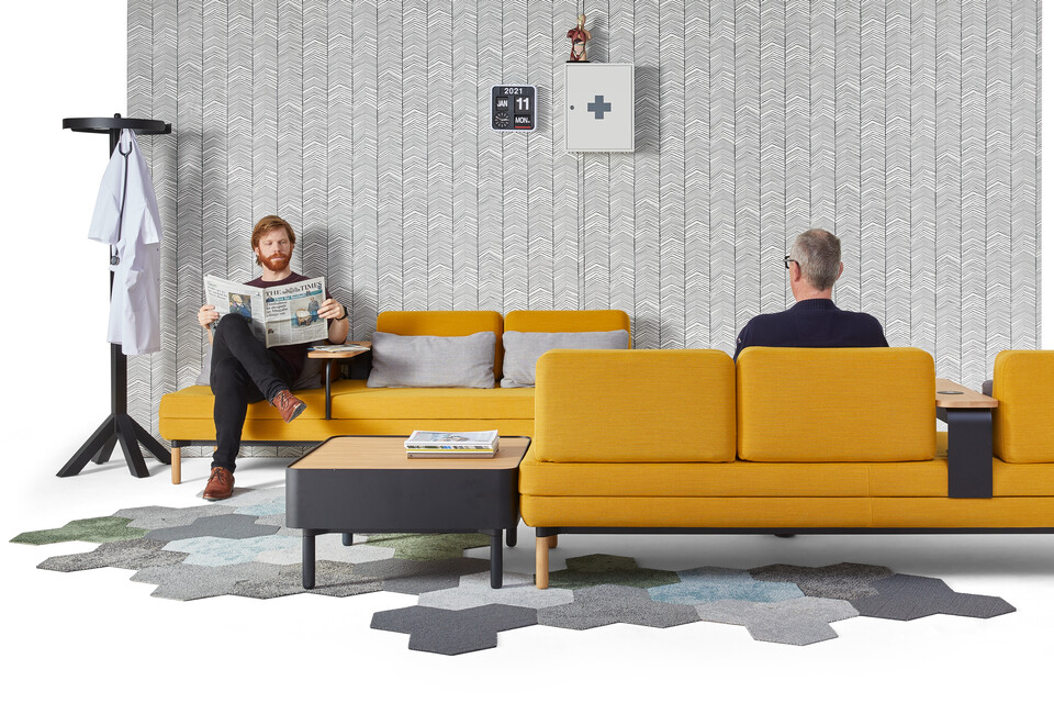 Gispen STEE sofas in black upholstered in yellow with black coffee table and oak top with black Dukdalf coat stand with male models front view