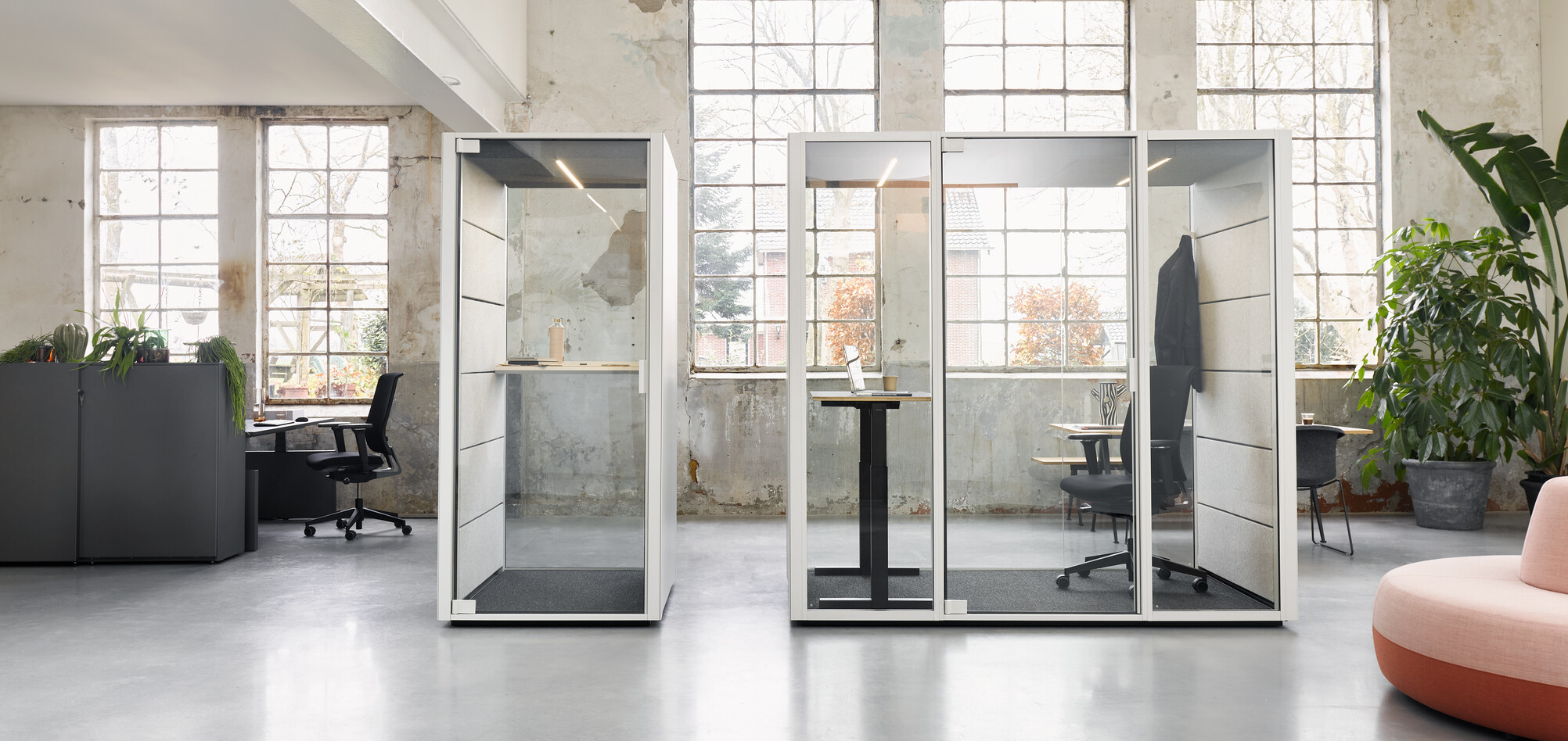 Ahrend Qabin booth and space in space with Ease office chair and black stand desk with Balance SDK Recharge and Well in a Hybrid working community setting