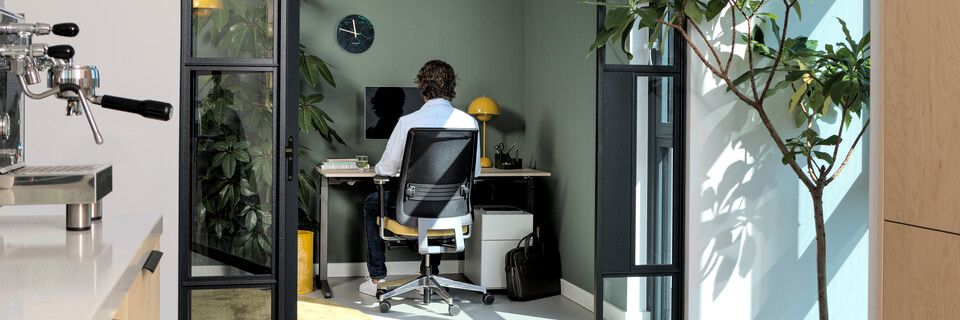 Royal Ahrend balance workstation in grey with oak tabletop with Ease office chair in yellow with male model interior view