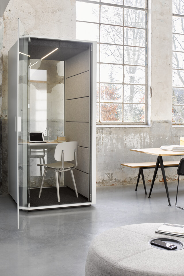 Ahrend Qabin booth in grey with grey Revolt chair and grey Recharge with Pyramid and Well armchair in a Hybrid working community setting