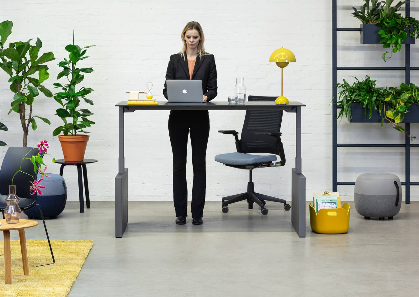 Royal Ahrend Balance Lift workstation in grey with charcoal top in stand position and 2020 office chair with female model standing front view