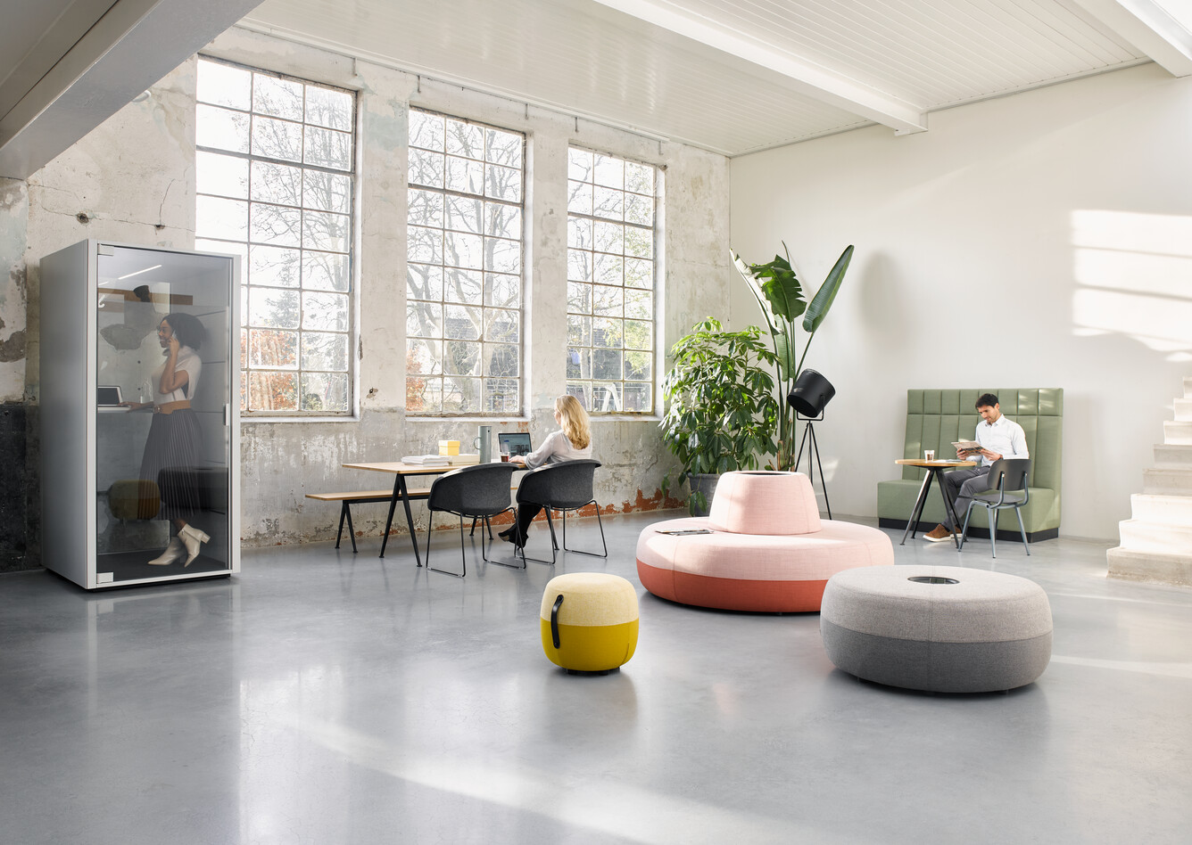 Ahrend Recharge poufs upholstered in pink yellow and grey with Qabin and Pyramid with Well armchairs and models in a Hybrid working community setting