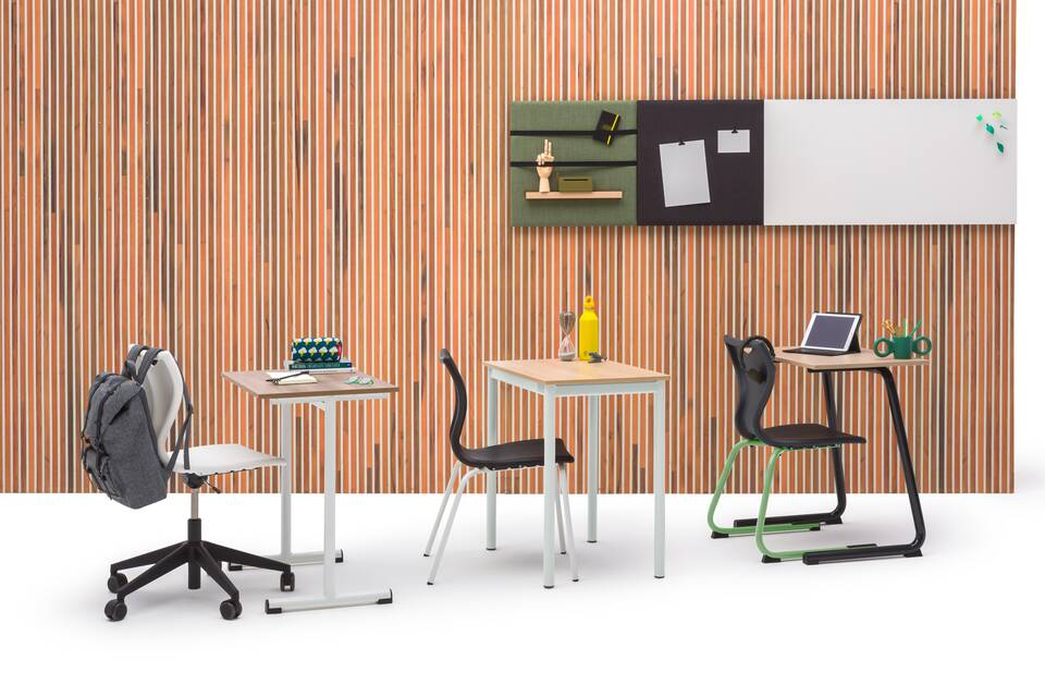 Gispen EDUU tables and chairs in classroom setup in front of brown wood patern backpanel front view