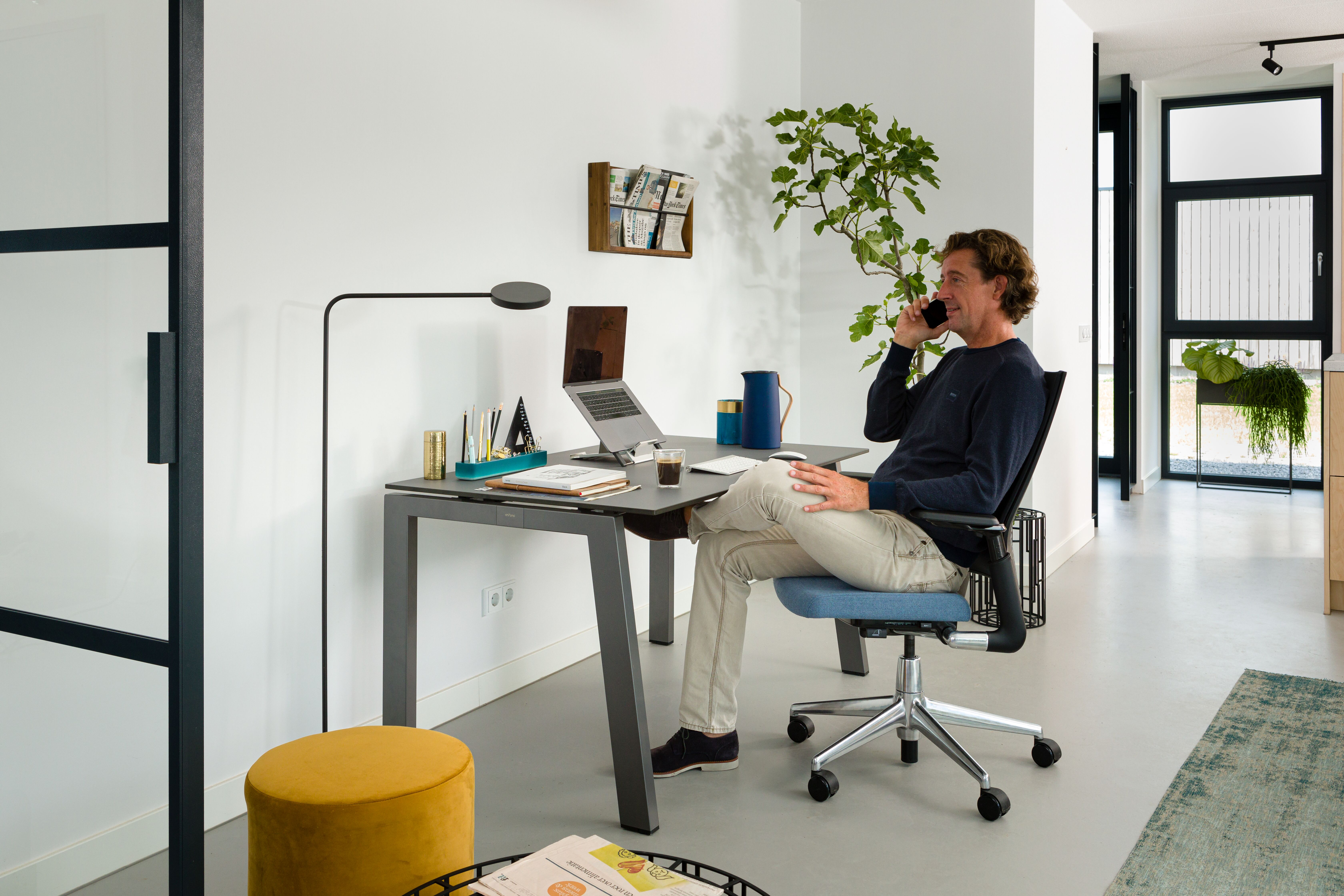 Royal Ahrend balance workstation in grey with charcoal tabletop and 2020 Extra Verta office chair upholstered in blue with male model calling interior view