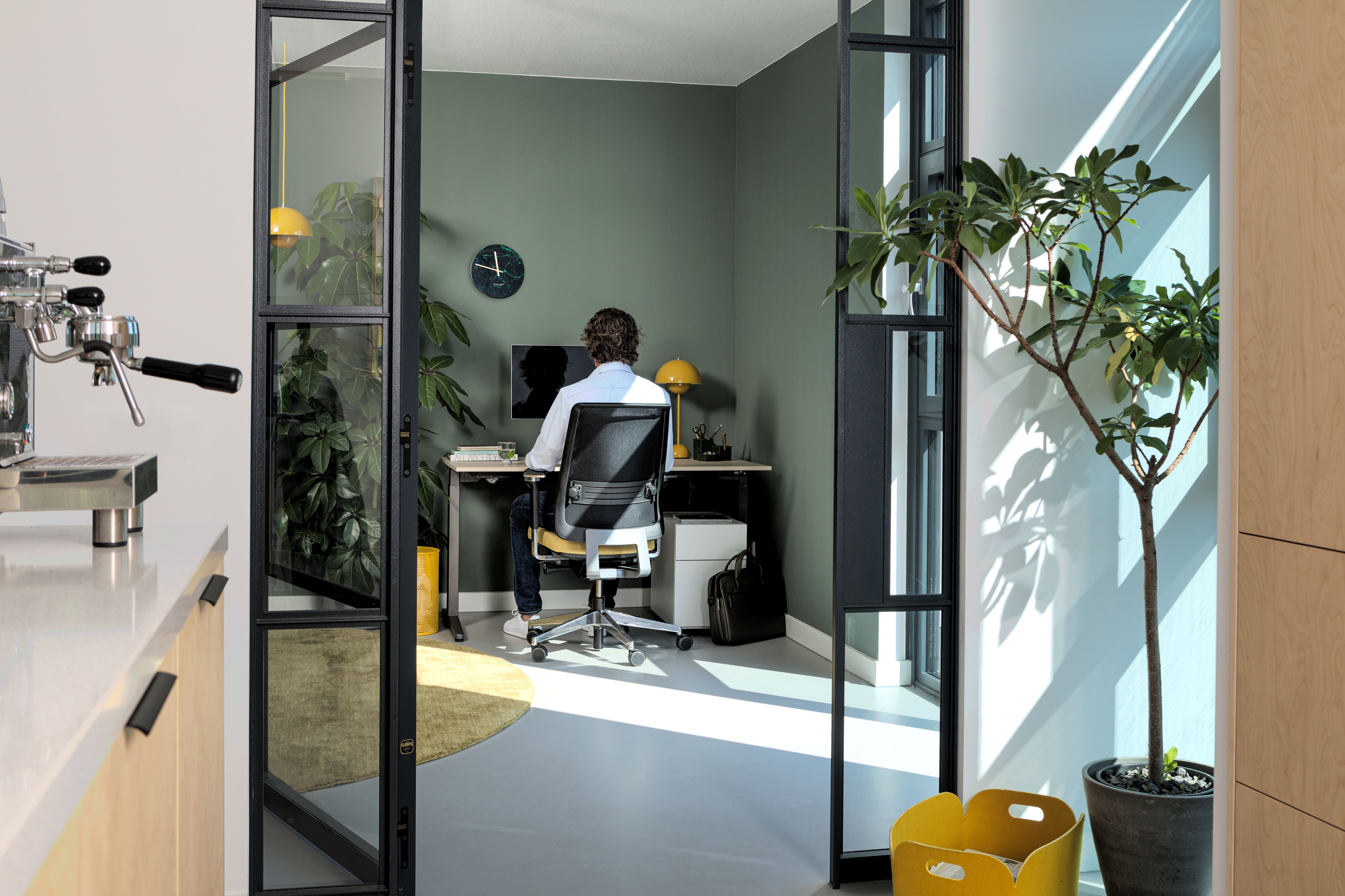 Royal Ahrend balance workstation in grey with oak tabletop and Ease office chair upholstered in yellow and black with male model interior view