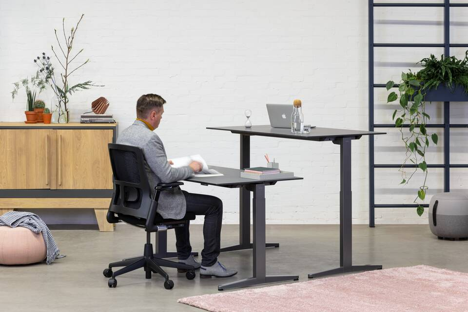 Royal Ahrend Balance Lift workstations in grey with charcoal tops and 2020 Verta office chair in black with male model front right view